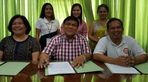 University President Dr. Oscar B. Cabañelez and DILG-Bukidnon provincial director Engr. Carmelo Enrique B. Libot (right), sign the memorandum of agreement to formalize the partnership. Dr. Joy M. Mirasol, VPREIA; CSDT dean Dr. Maribel Valdez; project leader Dr. Jiemalyn B. Paulican and an officer from DILG-Bukidnon, witness the signing. Office of the BukSU President photo